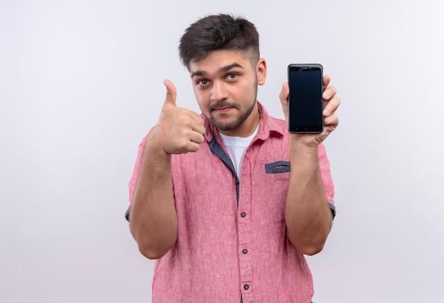 Jeune beau mec portant un polo rose louant le téléphone faisant super signe avec le pouce debout sur un mur blanc
