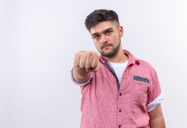 Jeune beau mec portant un polo rose montrant sérieusement le poing debout sur un mur blanc
