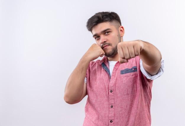 Jeune beau mec portant un polo rose montre la boxe debout sur un mur blanc