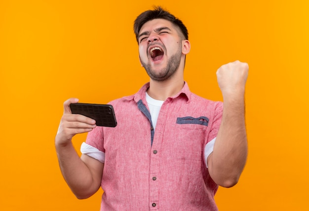 Jeune beau mec portant un polo rose se réjouissant de la victoire en tenant le téléphone en le faisant signer avec le poing levé debout sur le mur orange