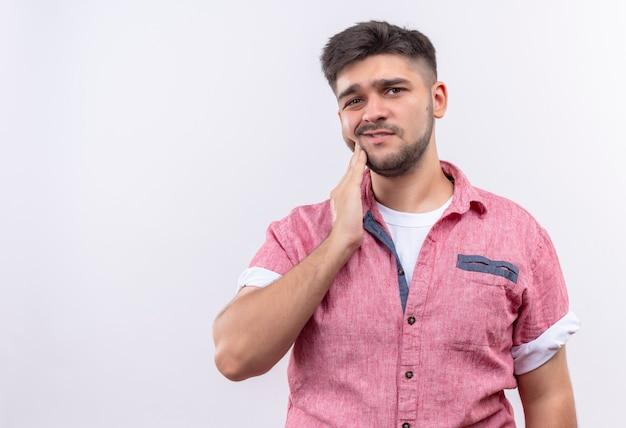 Jeune beau mec portant un polo rose souffrant de maux de dents tenant la joue avec la main debout sur un mur blanc