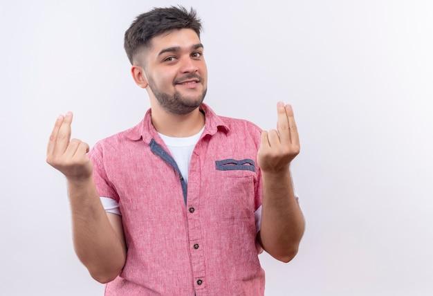 Jeune beau mec portant un polo rose souriant montrant signe d'argent avec les mains debout sur un mur blanc