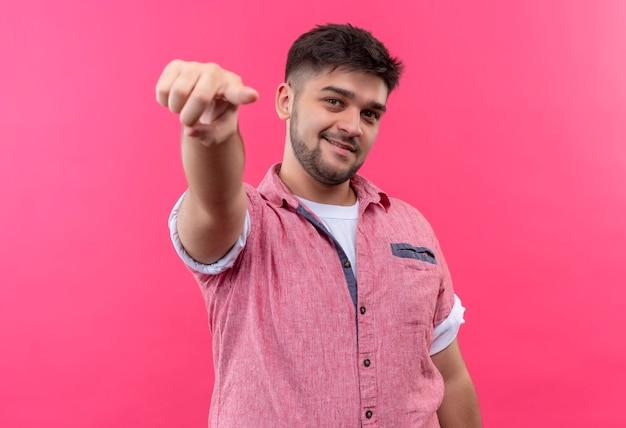 Jeune beau mec portant un polo rose souriant pointant sur vous debout sur un mur rose