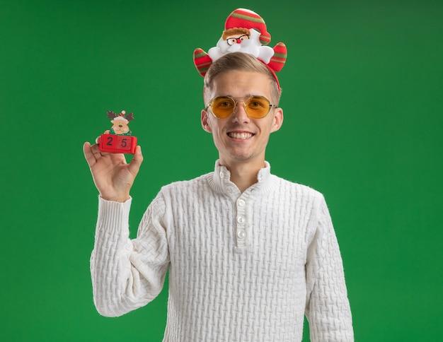 Jeune et beau mec souriant portant un bandeau de père noël avec des lunettes tenant un jouet de renne avec une date à la recherche d'isolement sur un mur vert