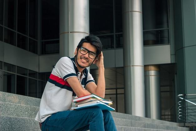 Jeune beau mec sourit et s'assoit avec des livres dans les escaliers