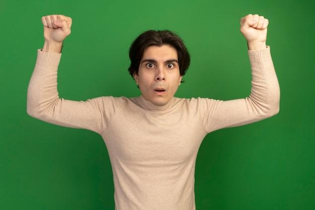Jeune beau mec surpris levant les poings isolés sur un mur vert