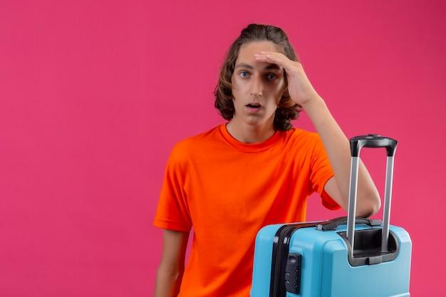 Jeune beau mec en t-shirt orange debout avec valise de voyage à la confusion et surpris avec la main sur la tête sur fond rose
