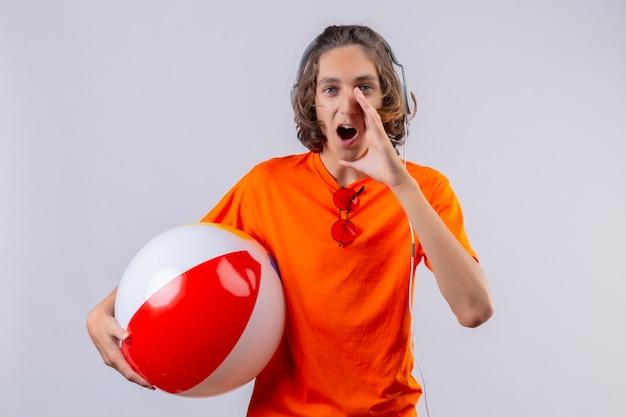 Jeune beau mec en t-shirt orange avec des écouteurs tenant un ballon gonflable en criant ou en appelant quelqu'un avec la main près de la bouche à la surprise debout sur fond blanc