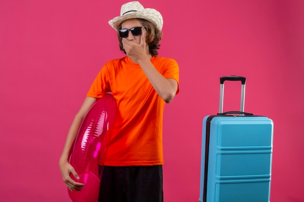 Jeune beau mec en t-shirt orange portant des lunettes de soleil noires tenant un anneau gonflable debout avec une valise de voyage à la surprise couvrant la bouche avec la main sur fond rose