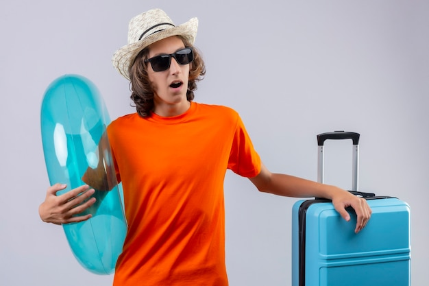 Jeune beau mec en t-shirt orange portant des lunettes de soleil noires tenant un anneau gonflable à la surprise debout avec valise de voyage sur fond blanc
