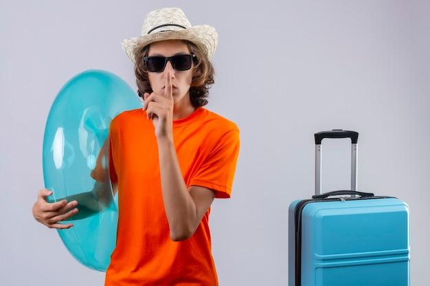 Jeune beau mec en t-shirt orange portant des lunettes de soleil noires tenant une bague gonflable faisant un geste de silence avec le doigt sur les lèvres debout avec valise de voyage sur fond blanc