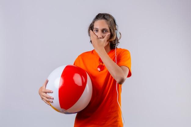 Jeune beau mec en t-shirt orange tenant ballon gonflable avec un casque étonné et surpris couvrant la bouche avec la main debout