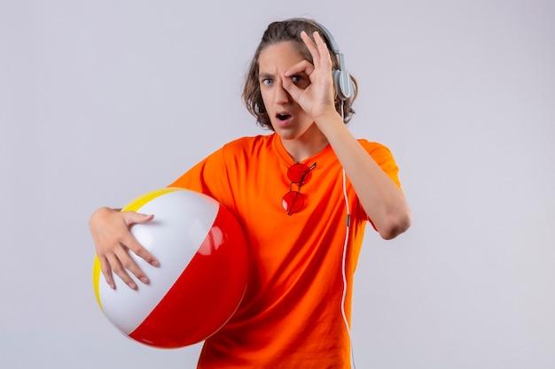 Jeune beau mec en t-shirt orange tenant ballon gonflable avec des écouteurs faisant signe ok regardant à travers ce signe surpris debout sur fond blanc