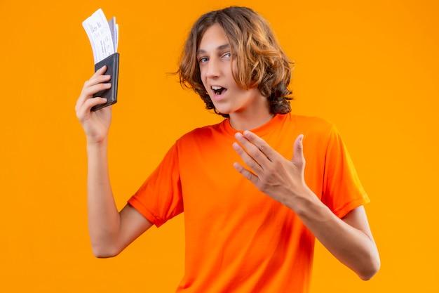 Jeune beau mec en t-shirt orange tenant des billets d'avion à la confiance positif et heureux debout sur fond orange