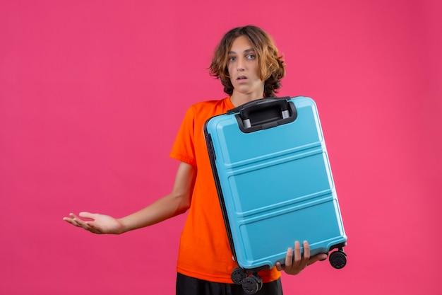 Jeune beau mec en t-shirt orange tenant une valise de voyage désemparé et confus n'ayant pas de réponse écartant les mains debout sur fond rose