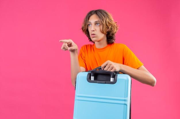 Jeune beau mec en t-shirt orange tenant une valise de voyage pointant du doigt vers quelque chose avec une expression de peur sur le visage debout sur fond rose