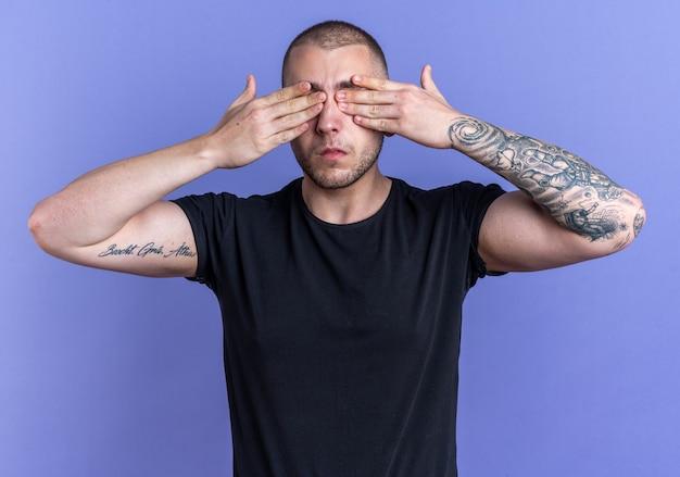 Jeune beau mec vêtu d'un t-shirt noir les yeux couverts avec les mains isolées sur le mur bleu