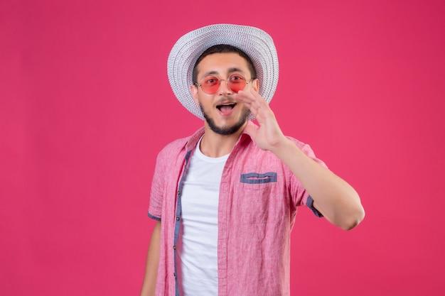 Jeune beau mec voyageur en chapeau d'été portant des lunettes de soleil appelant quelqu'un avec la main près de la bouche debout sur fond rose