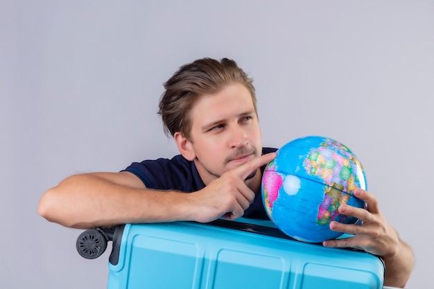 Jeune beau mec voyageur debout avec valise tenant le globe à côté avec une expression pensive pensant sur fond blanc
