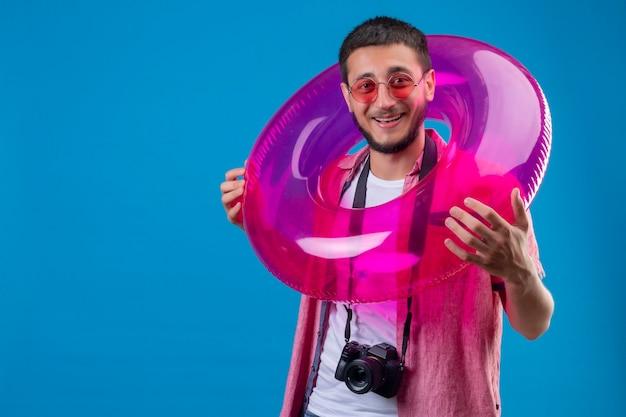 Jeune beau mec voyageur portant des lunettes debout avec anneau gonflable regardant la caméra avec un visage heureux souriant joyeusement debout sur fond bleu