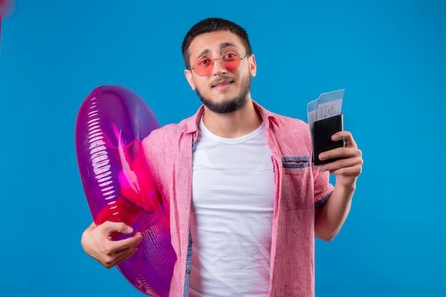 Jeune beau mec voyageur portant des lunettes de soleil tenant un anneau gonflable et des billets d'avion à la confusion debout sur fond bleu