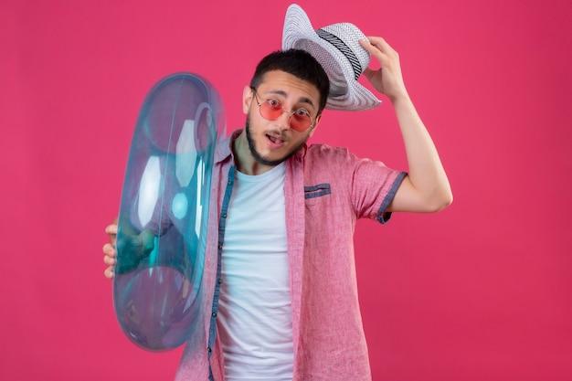 Jeune beau mec voyageur portant des lunettes de soleil tenant un anneau gonflable regardant la caméra étonné et surpris de remettre son chapeau d'été debout sur fond rose