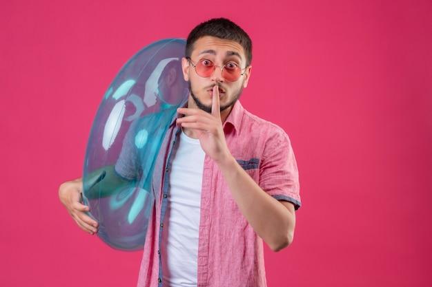 Jeune beau mec voyageur portant des lunettes de soleil tenant un anneau gonflable à la surprise de faire un geste de silence avec le doigt sur les lèvres debout sur fond rose