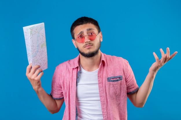 Jeune beau mec voyageur portant des lunettes de soleil tenant la carte désemparée et confus avec les bras levés n'ayant pas de réponse debout sur fond bleu