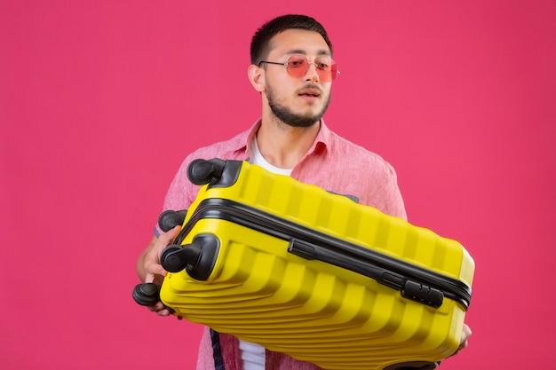 Jeune beau mec voyageur portant des lunettes de soleil tenant valise à côté avec une expression confiante sur le visage debout sur fond rose