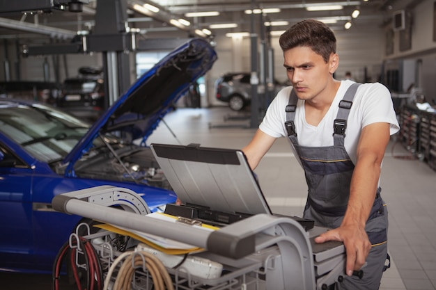 Jeune beau mécanicien en réparation de véhicule dans son garage