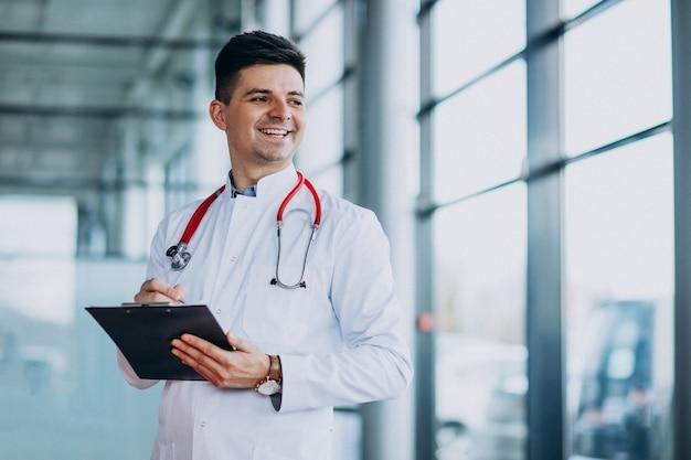 Jeune beau médecin dans un peignoir médical avec stéthoscope
