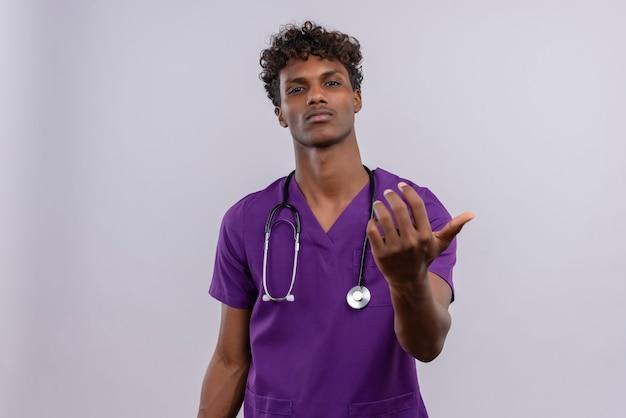 Un jeune beau médecin à la peau sombre avec des cheveux bouclés portant l'uniforme violet avec stéthoscope appelant quelqu'un à distance en criant en tournant à gauche tenant la main