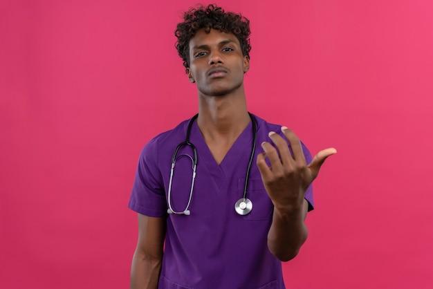 Un jeune beau médecin à la peau sombre confiant aux cheveux bouclés portant l'uniforme violet avec stéthoscope