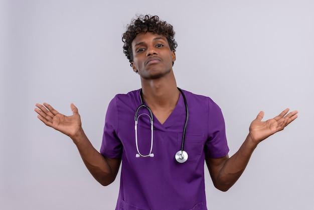 Un jeune beau médecin à la peau sombre confus avec des cheveux bouclés portant l'uniforme violet avec un stéthoscope ouvrant ses mains ne sais pas quoi faire