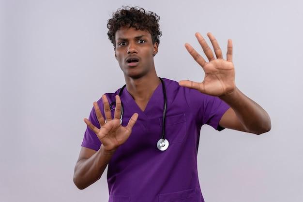 Un jeune beau médecin à la peau sombre mécontent avec des cheveux bouclés portant l'uniforme violet avec stéthoscope se serrant la main en aucun