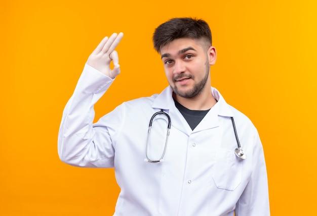 Jeune beau médecin portant une robe médicale blanche, des gants médicaux blancs et un stéthoscope à heureux de faire signe ok avec les doigts tanding sur mur orange