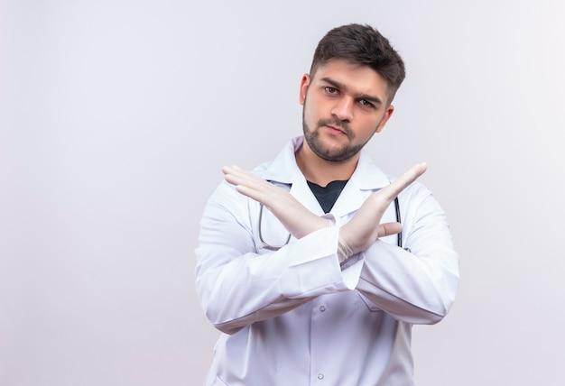 Jeune beau médecin portant une robe médicale blanche, des gants médicaux blancs et un stéthoscope insatisfait