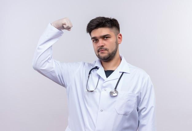 Jeune beau médecin portant une robe médicale blanche, des gants médicaux blancs et un stéthoscope montrant la puissance avec le poing levé debout sur un mur blanc