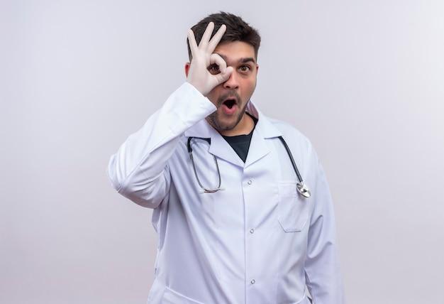 Jeune beau médecin portant une robe médicale blanche, des gants médicaux blancs et un stéthoscope montrant signe ok avec la main debout sur un mur blanc