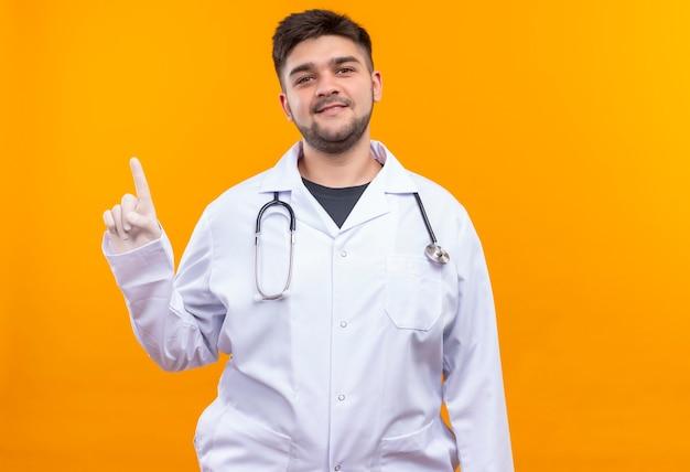 Jeune beau médecin portant une robe médicale blanche, des gants médicaux blancs et un stéthoscope souriant pointant vers le haut avec l'index debout sur un mur orange