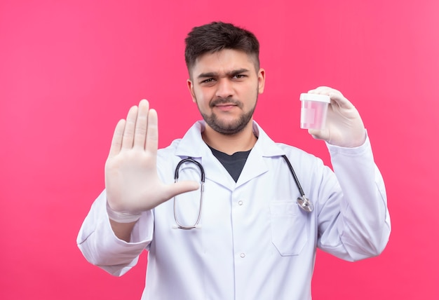 Jeune beau médecin portant une robe médicale blanche, des gants médicaux blancs et un stéthoscope, tenant un récipient d'analyse transparent faisant panneau d'arrêt avec la main debout sur le mur rose