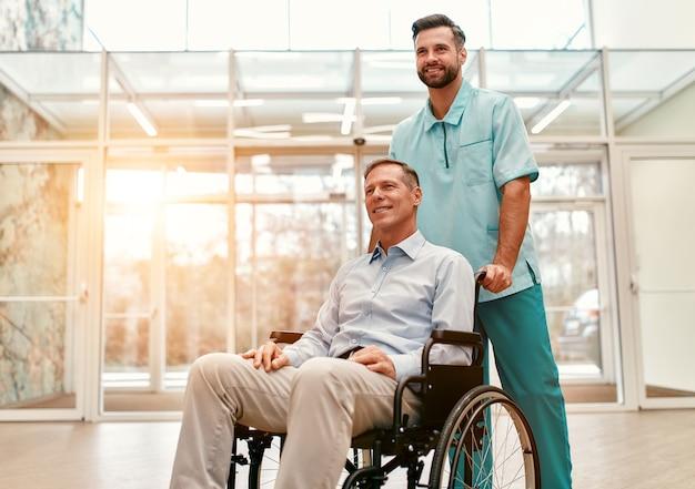 Un jeune beau médecin avec sa personne âgée handicapée en fauteuil roulant marche dans les couloirs d'une clinique moderne.
