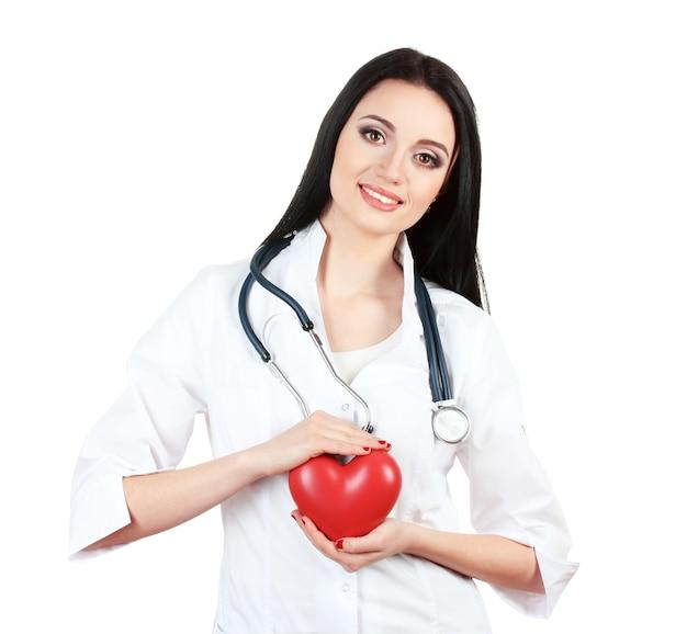 Jeune beau médecin avec stéthoscope tenant coeur isolé sur blanc