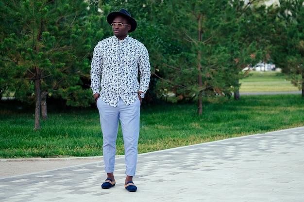 Un jeune et beau modèle afro-américain élégant dans un costume élégant et un chapeau noir dans un parc d'été. homme d'affaires hispanique latino-américain black posing at photoshoot