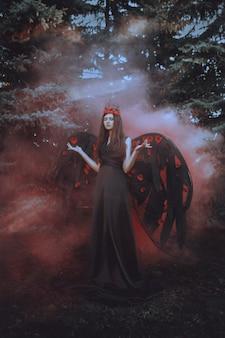 Jeune beau modèle dans une robe noire avec des ailes noires