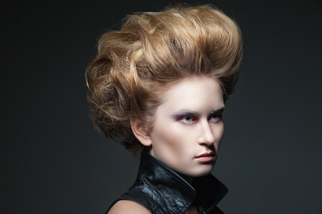 Jeune beau modèle féminin avec coiffure et maquillage regardant loin en arrière-plan uni.