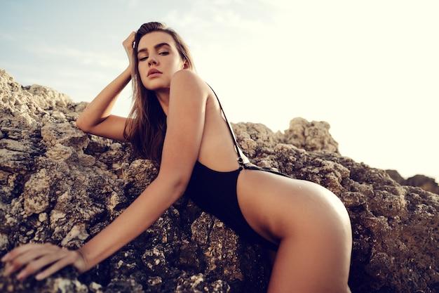Jeune beau modèle féminin sexy en bikini noir debout dans l'eau de mer près d'un énorme rocher