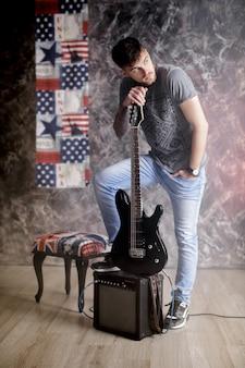 Jeune beau musicien avec guitare électrique sur fond sombre