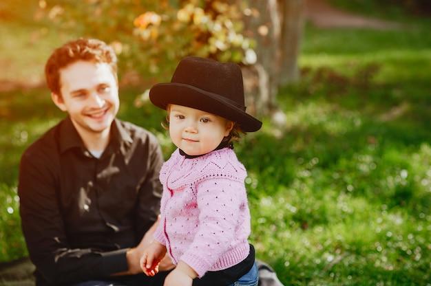 Jeune beau père jouant dans un parc de printemps avec petite fille