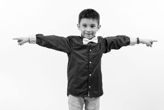 Jeune beau petit garçon isolé contre un mur blanc en noir et blanc